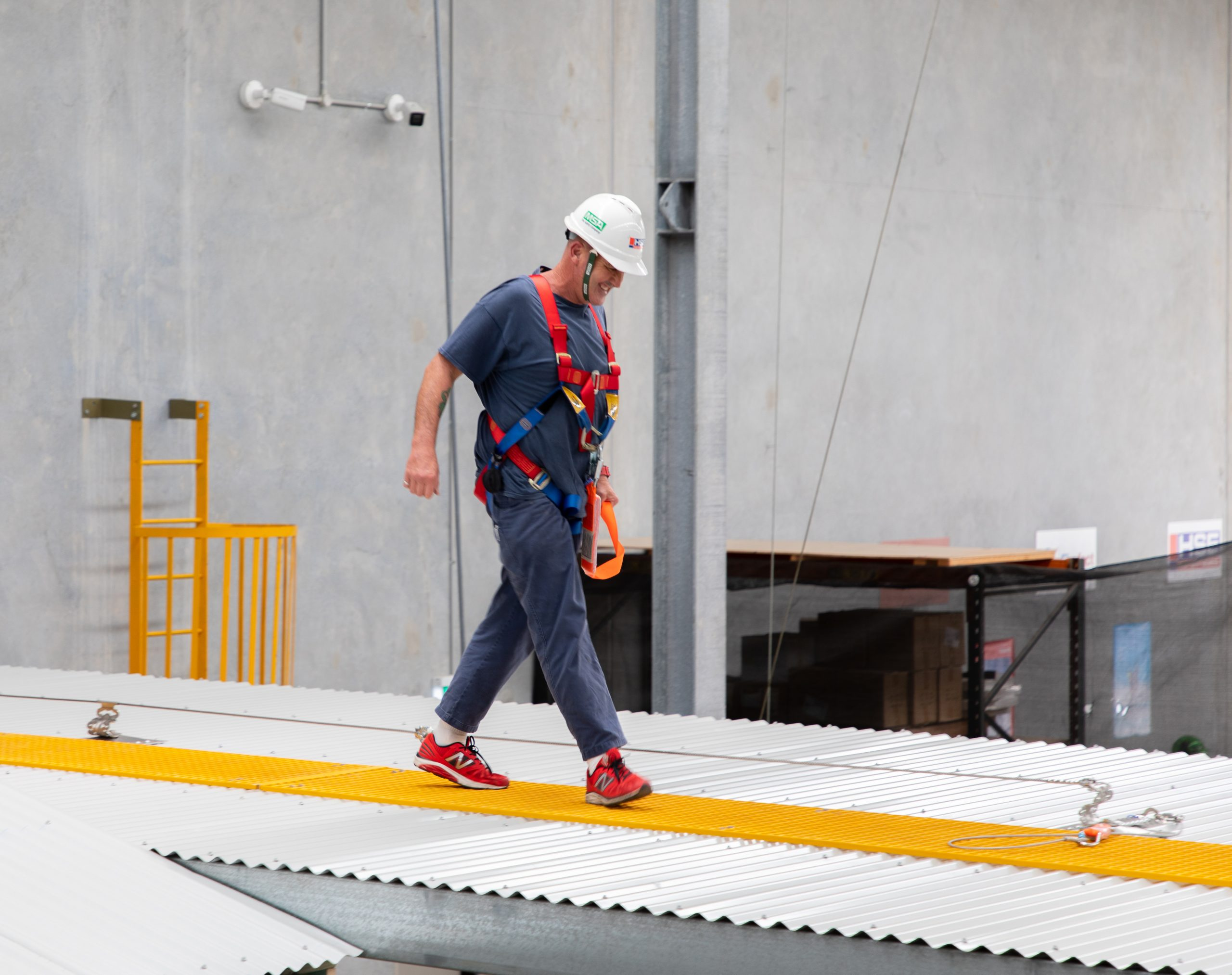 Participant using a static line on a flat roof as part of a work safely at heights training course.