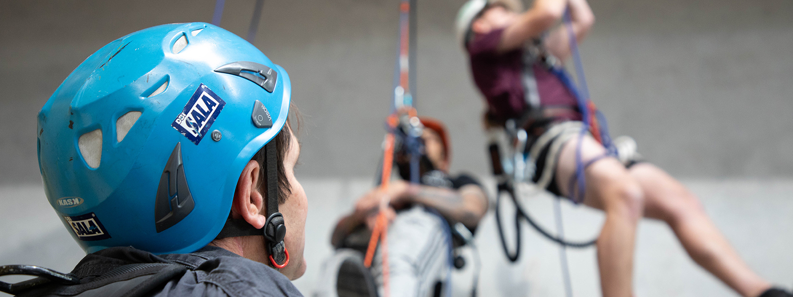 Instructor looks on as students practice vertical rope rescue techniques.