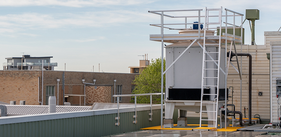Air-conditioning cooling tower on a roof with access ladder and safe working platform installed.