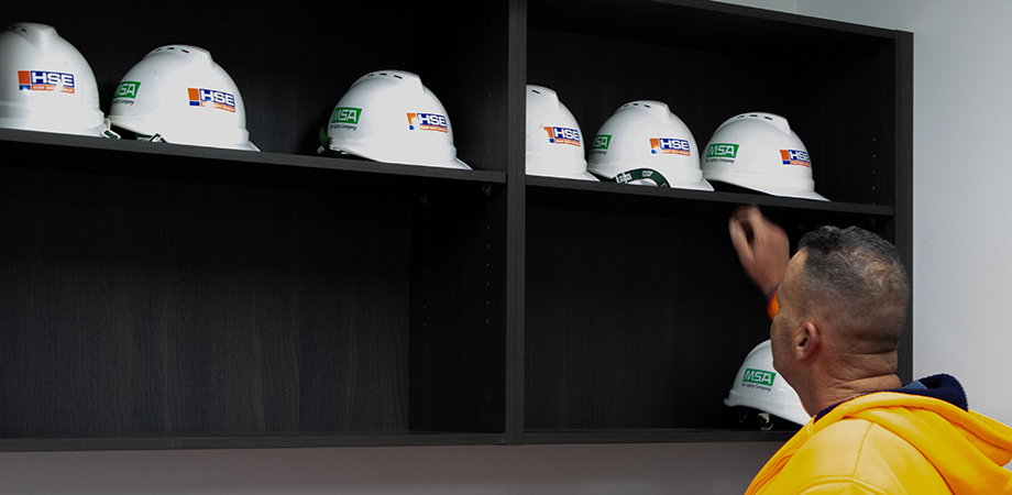 Student reaching for a hard hat.