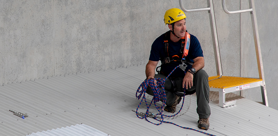 Worker using roof anchors to move across a sheet metal roof.