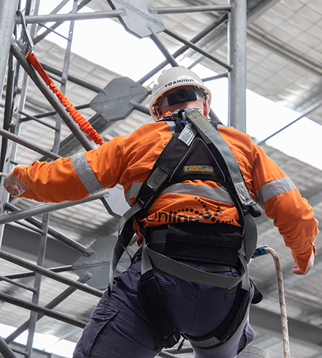 Scaling a communications tower using a twin-tail lanyard as fall arrest.