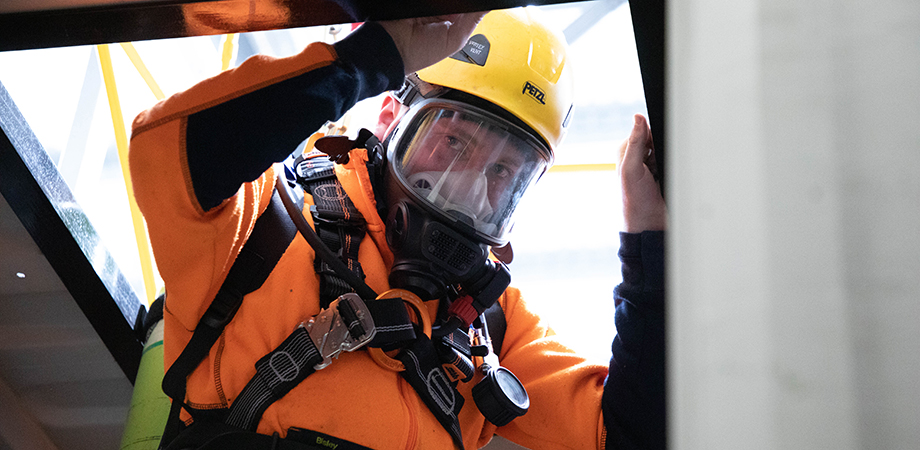 Participant in full breathing apparatus being lowered into a confined space.