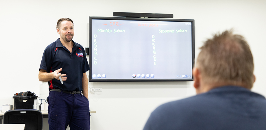 Trainer standing in front of an electronic whiteboard during a cardiopulmonary resuscitation class at Height Safety Engineers.